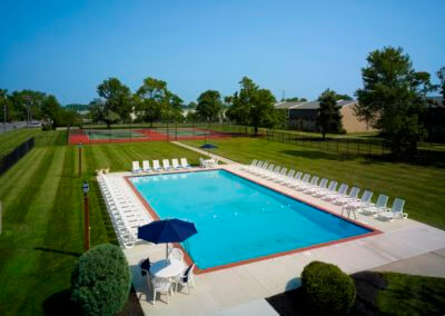 Outdoor swimming pool and tennis court at Korman at Cherrywood Apartments