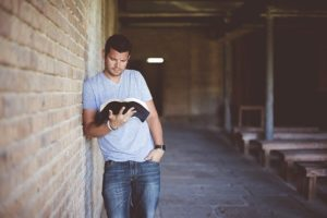 Man leaning against brick wall at a college reading a book